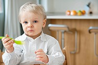 Boy eating with a fork and making a face