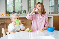 Girl drinking milk with her brother drinking juice at a breakfast table