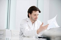 Male doctor examining a medical report