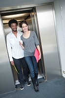 Businesswoman coming out from an elevator with her colleague