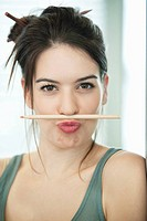 Woman balancing a pencil on lip