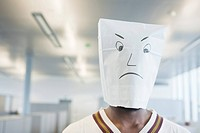 Businessman wearing a paper bag of sad face