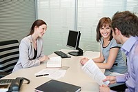 Female real estate agent and a couple discussing in an office