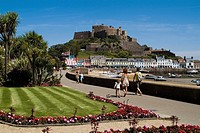 Gorey ST MARTIN JERSEY Tourist family walking on seafront promenade Mont Orgueil Castle