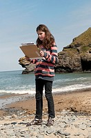 Primary school children surveying the beach at The Urdd Centre, Llangrannog, Ceredigion, West Wales UK