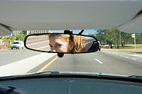 Woman driving, checking rear view mirror