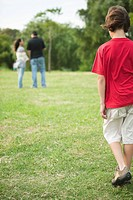 Boy walking sulkily toward parents having conversation distance