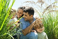 Family crouching together in tall grass (thumbnail)