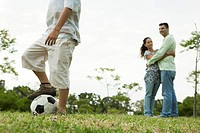 Boy playing with soccer ball, parents watching and embracing in background