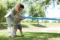 Mother helping young son play tug_of_war