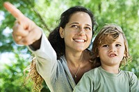 Mother pointing out something to young son outdoors