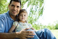 Father holding young daughter on lap outdoors (thumbnail)