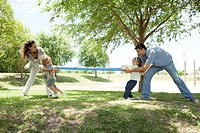 Family playing tug-of-war in park (thumbnail)