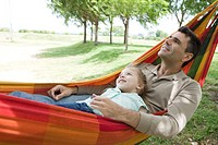 Father and young daughter relaxing together in hammock