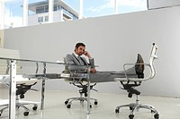 Businessman with legs on a chair