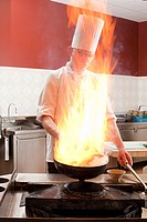 Male chef cooking food in commercial kitchen, flame over stove