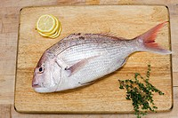 Fish on wooden chopping board