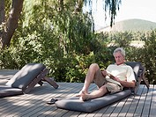 Senior man reading on sun lounger