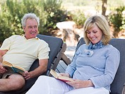 Mature couple reading on loungers in garden