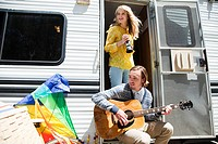 Young couple by caravan with guitar and video camera