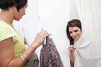 Sales assistant and woman trying on clothes