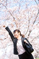 Businesswoman with arms raised under cherry blossoms
