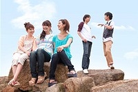 Five young people on rocks, smiling