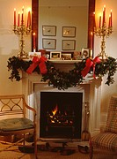 Fresh holly and ivy Christmas garland on mantelpiece with lighted candles in candelabra below mirror