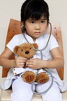 young girl playing doctor with bear