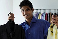 young man holding up two shirts and smiling