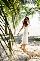 young woman walking on beach with coconut trees in background