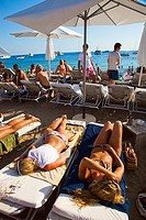 Young people on the beach Blue Marlin Bar. Jondal Beach. Sant Josep de sa Talaia. Ibiza. Balearic Islands. Spain.