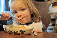 little girl eating cooked vegetable with a spoon from a plate, 2 years old