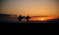 Hawaii, Oahu, Waikiki, Two Surfers walking along the shoreline as the beautiful sunsets