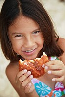 Hawaii, Oahu, Young girl enjoying a malasada.