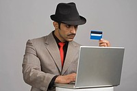 Actor portraying a businessman holding a credit card and working on a laptop