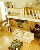Bedroom on mezzanine above kitchen and dining room and living room with large cream sofa on wooden flooring