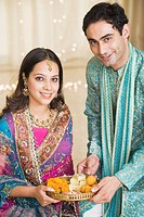 Couple holding a pooja thali of Diwali and smiling