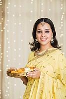 Woman holding a pooja thali of Diwali