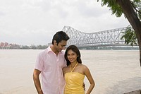 Couple smiling with a bridge in the background, Howrah Bridge, Hooghly River, Kolkata, West Bengal, India