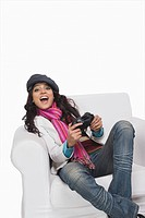 Woman sitting in an armchair and playing video game
