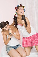 Two women singing into a hairbrush