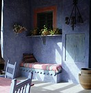 Pink striped rug on built in seating below plants on shelf in purple Mexican_style dining room