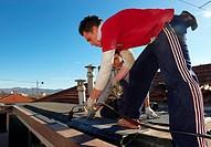 muratori sul tetto di una casa mettono uno strato di catrame isolante