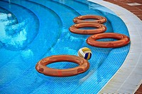 Flotation devices rescue rings or life buoys and a volleyball floating in water by the poolside