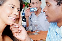 Close_up of a young couple looking at each other with a young man taking a picture