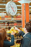 Rear view of a young couple weighing apples on a weighing scale in a supermarket