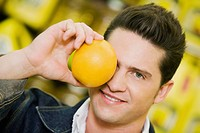 Close_up of a young man covering his eye with an orange