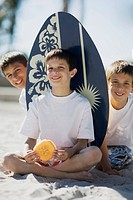 Portrait of two boys and a teenage boy sitting on the beach and smiling