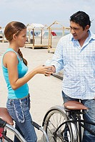 Side profile of a mid adult man giving ice_cream to a young woman